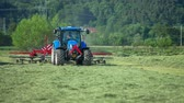 machinery : It is a perfect hot summer day for working out in the fields. A young farmer is driving a blue tractor and he is raking hay. Stock Footage