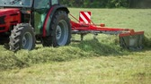 t��o : A red tractor is preparing hay with a rotary hay rake. A farmer is working hard outside on this summer day.