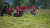 t��o : Freshly cut grass is flying out of the machinery. A young farmer is working really hard on this warm summer day.