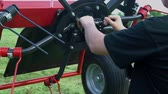 machinery : A farmer is adjusting the wheel on the agricultural machinery rakes. He fixes it and then he goes away.