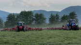 machinery : Three large tractors are working on the big grass field and they are preparing hay. They are using agricultural machinery. Stock Footage