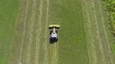 tenure : A yellow tractor is driving across the grass field and it is slowly cutting grass with a big machinery. It is a nice summer day. Heli shot. Stock Footage
