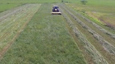 tenure : A tractor is cutting high grass with a special agricultural machinery. It is a nice summer day. Stock Footage