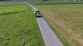 tenure : A yellow tractor is driving on a narrow country path. It is rushing to the grass field to start cutting grass with a grass cutting machinery. Stock Footage