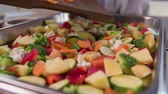 roast ham : Adding orange carrot on the board to vegetables placed in the tray. There is a mixure of healthy vegetables like zucchini, cauliflower, orange carrot, red peppers, potatoe and broccoli. Stock Footage