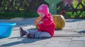 squash family : A toddler is playing with an object and then she throws it on the ground. She is sitting on the ground outside.