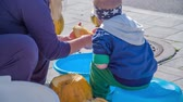 squash family : Its Halloween time. A small boy is helping his mom clean the pumpkins and is putting the pumpkin seeds into a big blue bucket.