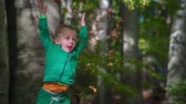 košíček : A small boy is playing with leaves in the forest. He throws them up in the air and watches them how they fall on the ground.