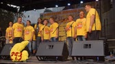 hostia : A few men singers are singing on stage. They are all wearing yellow T-shirts.