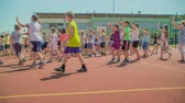 işe : GRIZE, SLOVENIA - 10. JUNE 2017  Small kids are standing on the sport facility outside the school and are waving at someone. Its summer time and they are spending time outdoors during their PE. Stok Video