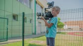işe : GRIZE, SLOVENIA - 10. JUNE 2017  A boy is holding a big camera and he is recording something. They are having an acting class.