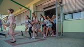 seção : GRIZE, SLOVENIA - 10. JUNE 2017  Secondary school children are pushing the school door and they run out the door because the summer is finally here.
