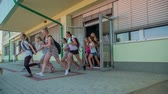 seção : GRIZE, SLOVENIA - 10. JUNE 2017  Secondary school children open the school door and run out the door because the summer holidays are here.