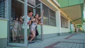 seção : GRIZE, SLOVENIA - 10. JUNE 2017  Children look happy and are smiling when they are running out the school door. The school year is over and the summer holidays are here.
