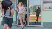 işe : GRIZE, SLOVENIA - 10. JUNE 2017  Children open the front door of the school and they run out. The school is officially over and they are happy to have summer vacation.