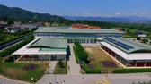 işe : GRIZE, SLOVENIA - 10. JUNE 2017  There is a narrow path which is leading to the entrance of the school. Aerial shot. Its summer time. Stok Video