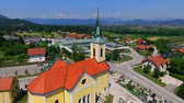 seção : GRIZE, SLOVENIA - 10. JUNE 2017  A yellow church is located in the middle of a village. There is a cemetary next to it. Aerial shot. Stock Footage