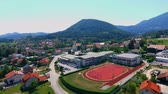seção : GRIZE, SLOVENIA - 10. JUNE 2017  A big red sport facility is located outside the school. Aerial shot. Its summer time. The Slovenian landscape is gorgeous. Stock Footage
