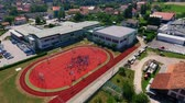 işe : GRIZE, SLOVENIA - 10. JUNE 2017  A big school with a basketball court outside the school. Aerial shot. The school is situated in a small village.