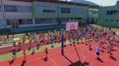 seção : GRIZE, SLOVENIA - 10. JUNE 2017  Children start running across the basketball court. They are having fun and are doing different sports activities. Its summer time. Aerial shot.