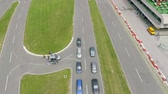 escorregadio : There are seven cars waiting in a row on the road. Aerial shot. Its spring time.