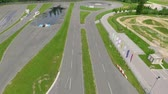 kaygan : A car is driving on a road in a safe driving center. Aerial shot. Its a sunny and warm day.