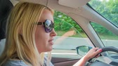 young elephants : A woman with blond hair is driving a car on a highway. The whole family is going to visit the zoo in the capital of Slovenia. Stock Footage