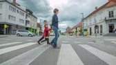 пешеход : ZALEC, SLOVENIA JUNE 10th 2017 A young woman with two children is crossing the street at zebra crossing. This town looks very neat and beautiful.