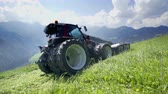 ancinho : A tractor is slowly driving uphill and cutting grass up in the mountains on a gorgeous summer day. Vídeos