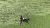 fodder : A tractor is pulling a big machinery behind it and it is cutting grass with it. Aerial shot. Its summer time. Stock Footage