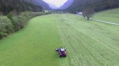 ancinho : A farmer is driving a tractor and he needs to cut grass on a big grass field here in the Logar Valley. Its summer time. Aerial shot.