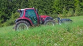 mowing : A red tractor is standing still in the middle of the hill. Its summer time.