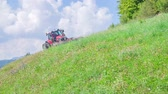 mowing : A farmer is cutting grass wth grass cutting machinery when he is driving on a steep hill.