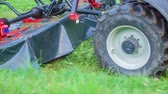 mowing : A tractor is driving on the green grass and he is connected to the grass cutting machine. Stock Footage
