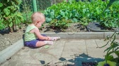 family love : Cute little girl sitting on the dirty ground in the garden on a hot sunny day.