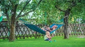 függőágy : Young mother and her son relaxing and swinging in hammock while little cute baby girl sits on the lawn and plays with pink flip flops.