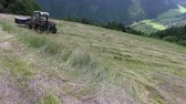 곤포 : The grass has been cut and farmers are now preparing hay. The tractor is driving uphill.