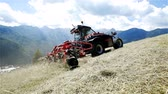ancinho : A tractor is driving on the hill and the agricultural machinery is organizing hay. The day is sunny and the view in the back is breath-taking.