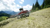 ancinho : Big rakes are turning hay around when a farmer is preparing hay with his tractor and agricultural machinery.
