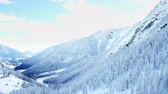 chalet : The trees on the mountains are covered with snow. The day is beautiful and sunny. Stock Footage