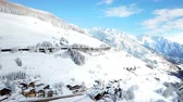 chalet : The landscape is completely covered with snow. The sky is beautifully blue and the sun is shining. Stock Footage