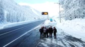 chalet : A few people are standing by the main road and are waving. There is snow everywhere. Its winter time. Stock Footage