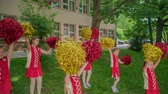 matraque : Holding their yellow and red pom-poms and practising the choreo for their performance. Vidéos Libres De Droits