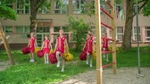 asa : Pupils are practising the choreo with pom-poms in the school yard. They are wearing red constumes. Stok Video