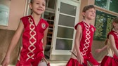 matraque : Beautiful small girls are majorettes. They are weaing red costumes and are holding majorette sticks.