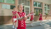 rytmický : Happy girls are practising their dancing outside of school. Theyre holding the majorette sticks.