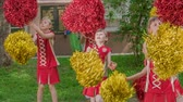 street parade : Girls are dancing with pom-poms. Theyre practising the routine for the school performance.