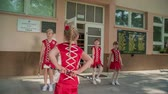 matraque : Girls are really happy dancing in front of the school. They are wearing red costumes and are practising with majorette sticks.