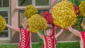 matraque : Primary school girls are holding yellow and red pom-poms and are practising for their school performance.