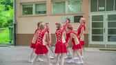 rytmický : Majorettes are about to start performing and they look very excited. They are wearing red costumes.